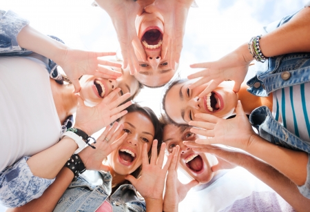 hanging on: summer holidays and teenage concept - group of teenagers looking down and screaming Stock Photo