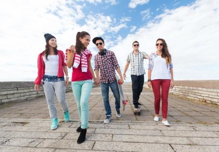 zomervakantie en tiener concept - groep van tieners met schaatsen buiten Stockfoto