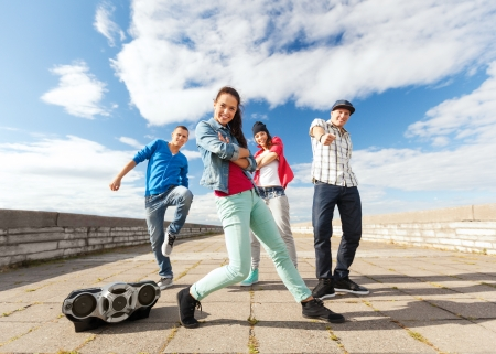 sport, dancing and urban culture concept - group of teenagers dancing photo