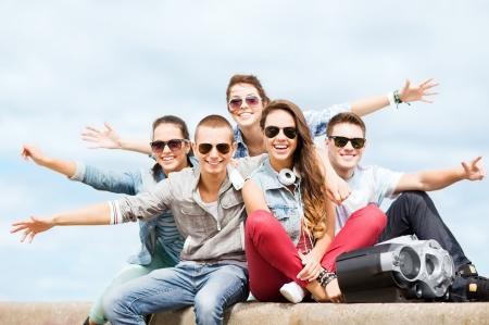 zomervakantie en tiener concept - groep tieners opknoping buiten