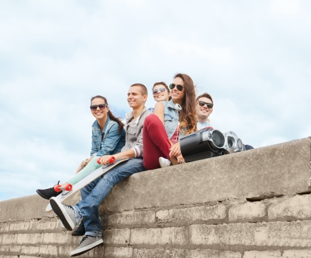 boom box: summer holidays and teenage concept - group of teenagers hanging outside Stock Photo