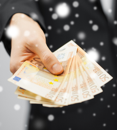 christmas profits: picture of man in suit with euro cash money