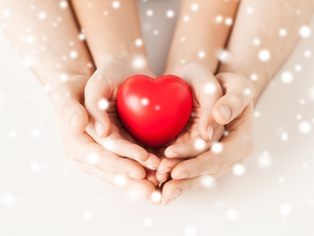 child couple: close up of woman and man hands with heart