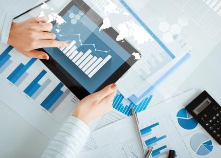 bedrijf, kantoor, school en onderwijs concept - vrouw met tablet pc en grafiek papieren