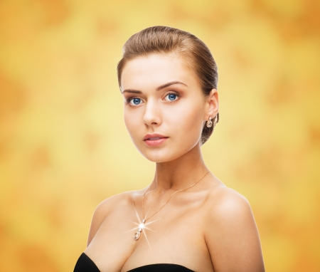 beauty and jewelry concept - woman wearing shiny diamond earrings and pendant photo