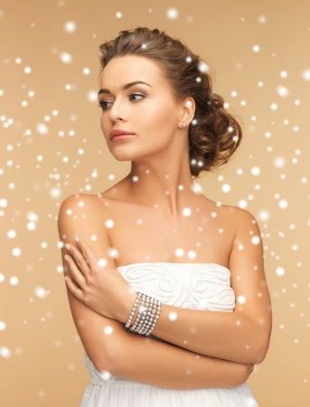 christmas beads: beauty and jewelery concept - beautiful woman with pearl earrings and bracelet