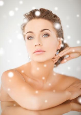 rich woman: beauty and jewelery concept - woman wearing shiny diamond earrings Stock Photo