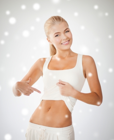 picture of beautiful sporty woman pointing at her abs photo