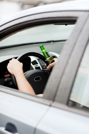 intoxicated: transportation and vehicle concept - man drinking alcohol while driving the car