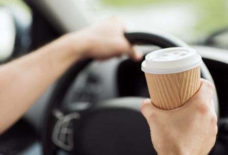 교통 및 차량의 개념 - 차를 운전하는 동안 커피를 마시는 사람