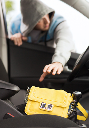 thieves: transportation, crime and ownership concept - thief stealing bag from the car Stock Photo