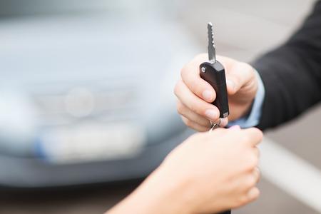 concept de transport et de la propriété - client et le vendeur avec la clé de voiture à l'extérieur