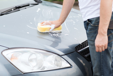transportation and ownership concept - man washing a car photo