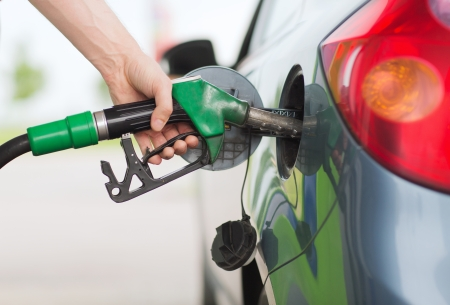 green fuel: transportation and ownership concept - man pumping gasoline fuel in car at gas station