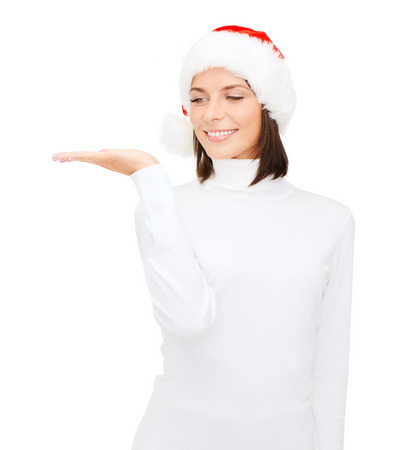 christmas, x-mas, winter, happiness concept - smiling woman in santa helper hat with something on palm photo
