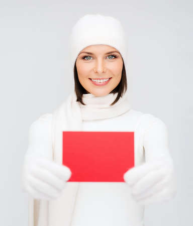christmas, x-mas, people, advertisement, sale concept - happy woman in winter clothes with blank red card photo