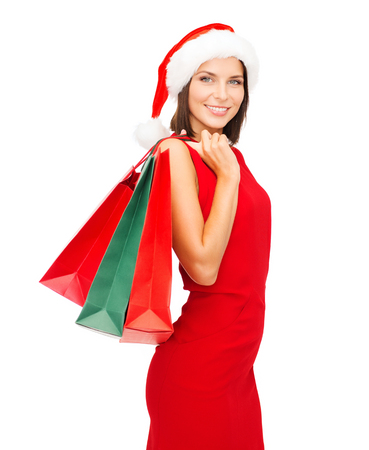 shopping, sale, gifts, christmas, x-mas concept - smiling woman in red dress and santa helper hat with shopping bags photo