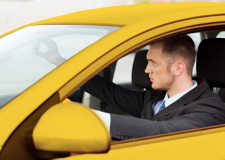 yellow car: transportation and vehicle concept - businessman or taxi driver driving a car