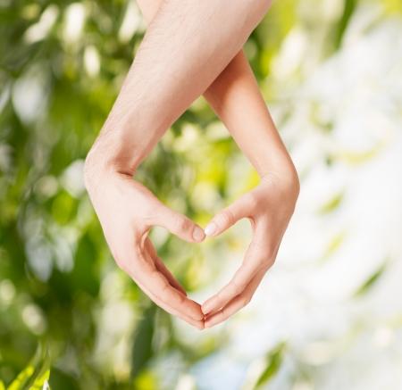 Öko-, Bio-, Natur, Liebe, Harmonie-Konzept - Frau und Mann Hände zeigen Herz-Form