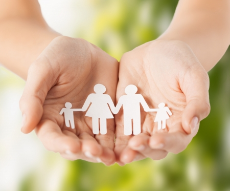 eco, bio, nature, love, harmony concept - woman cupped hands showing paper man family Stock Photo