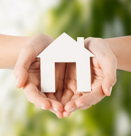 eco, bio, home, nature, power saving concept - woman hands holding house photo