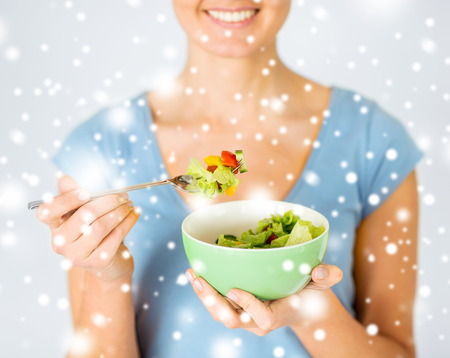 light diet: healthy food and kitchen concept - woman eating salad with vegetables