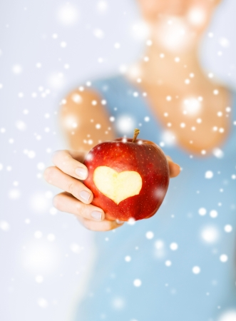 healthy food and lifestyle - woman hand holding red apple with heart shape