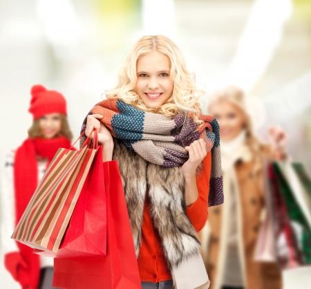 ropa de invierno: venta al por menor y venta concepto - adolescentes felices en ropa de invierno con bolsas de la compra