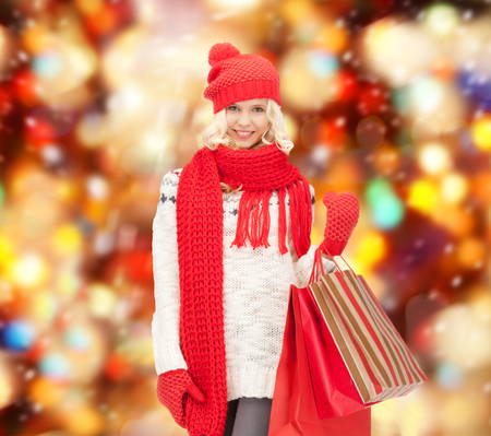 holidays, sale, christmas concept - beautiful teenage girl in winter clothes with shopping bags photo