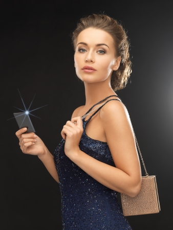 luxury, wealth, premium membership, nightlife concept - beautiful woman in evening dress with small bag photo