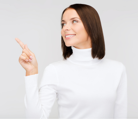 winter, people, happiness concept - woman in white sweater pointing to something photo