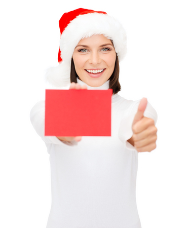christmas, x-mas, people, advertisement, sale concept - happy woman in santa helper hat with blank red card showing thumbs up photo