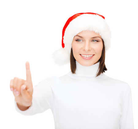 christmas, x-mas, winter, happiness concept - smiling woman in santa helper hat pressing vitrual button photo