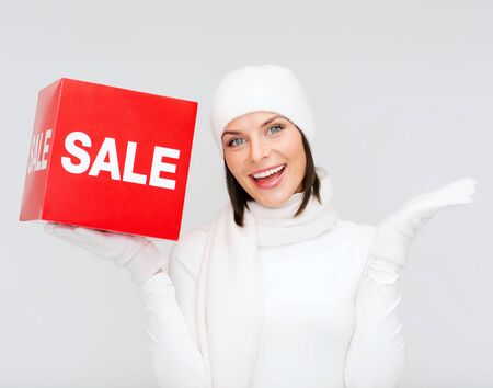 shopping, gifts, christmas, x-mas concept - smiling woman in winter clothes with red sale sign photo