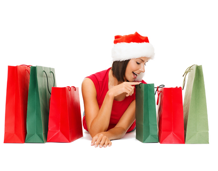 shopping, sale, gifts, christmas, x-mas concept - smiling woman in red shirt and santa helper hat with shopping bags photo
