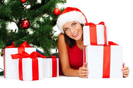 christmas, x-mas, winter, happiness concept - smiling woman in santa helper hat with many gift boxes and tree Stock Photo - 22381217
