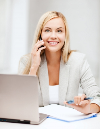 business and education concept - picture of businesswoman with laptop and cell phone photo