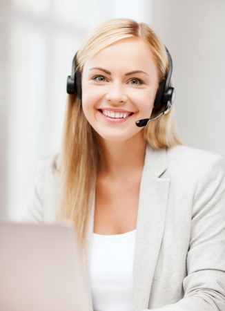 helpline: business, call centre and technology concept - female helpline operator with headphones and laptop pc