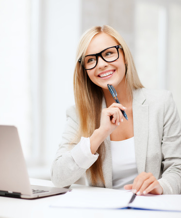 business and education concept - indoor picture of smiling woman with documents and pen photo
