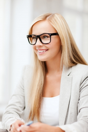 business and education concept - indoor picture of smiling woman with eyeglasses photo