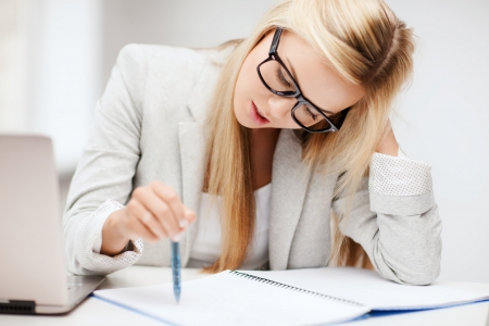 confused person: business and education concept - indoor picture of bored and tired woman taking notes