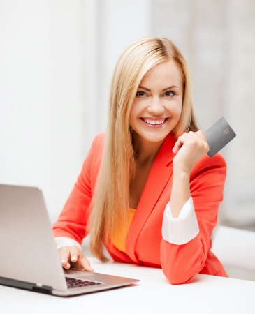 business and internet concept - smiling businesswoman with laptop using credit card Stock Photo
