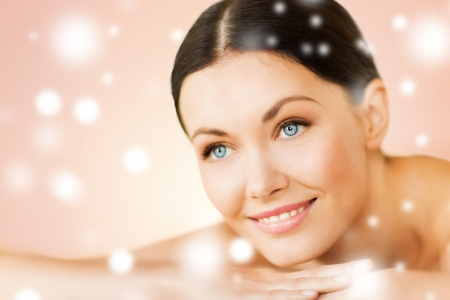 skincare facial: health and beauty concept - woman in spa salon lying on the massage desk