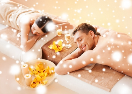 therapeutic massage: health and beauty, honeymoon and vacation concept - couple in spa salon lying on the massage desks