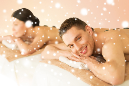 health and beauty, honeymoon and vacation concept - couple in spa salon with hot stones photo