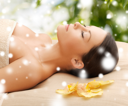 health and beauty concept - woman in spa lying on the massage desk photo