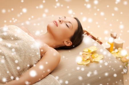 therapeutic massage: health and beauty concept - woman in spa salon lying on the massage desk