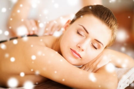 health and beauty concept - woman in spa salon with hot stones photo
