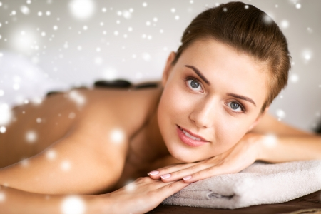 salon spa: health and beauty concept - beautiful woman in spa salon with hot stones Stock Photo