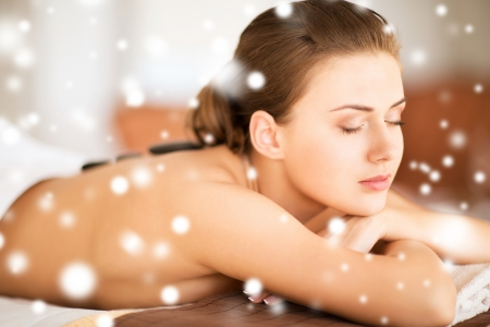health and beauty concept - - beautiful woman in spa salon with hot stones photo